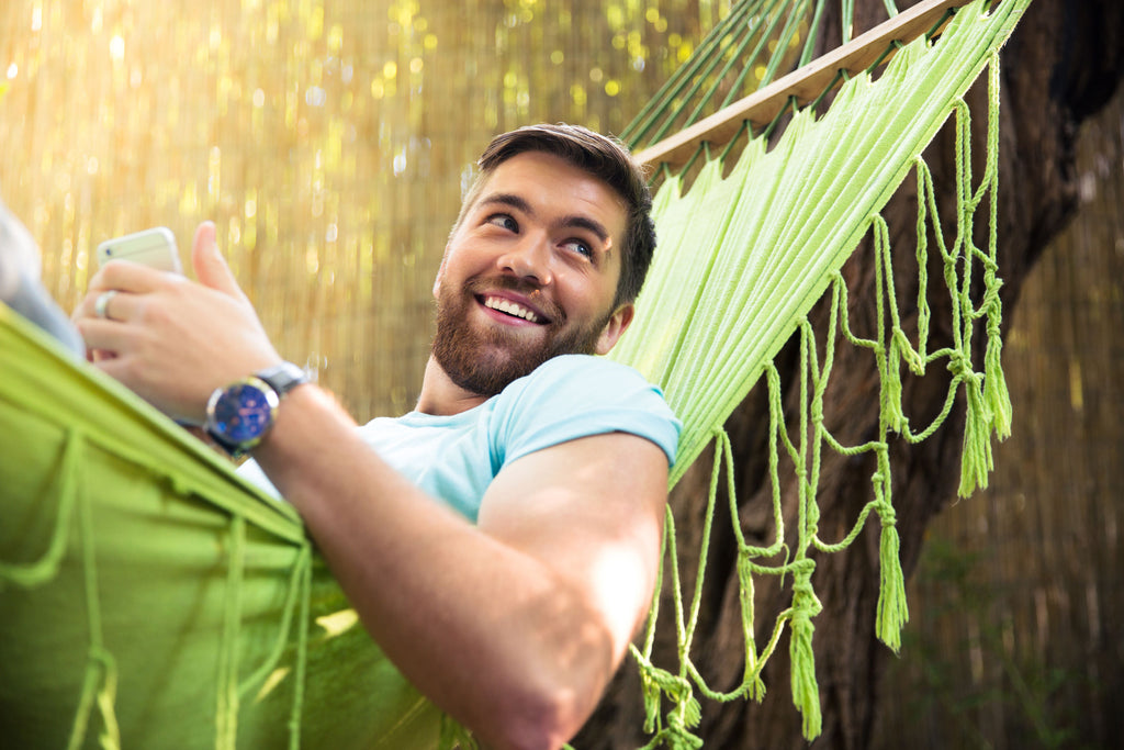 Man resting on hammock with smart phone in hand.