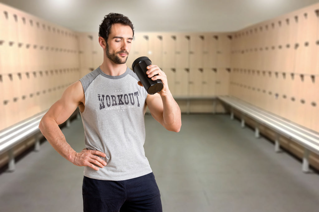 Man drinking protein in locker room after workout.
