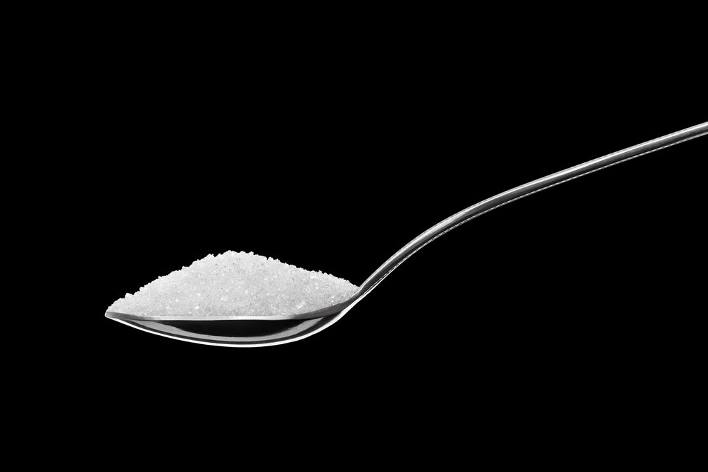 Spoon full of sugar on solid black background
