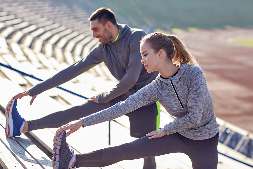 image of a male and female stretching on bleachers on a track
