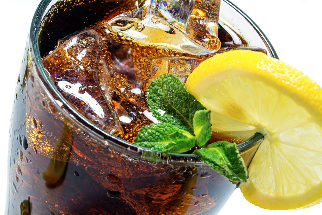 Brown soda in a glass with a lemon wedge on the side
