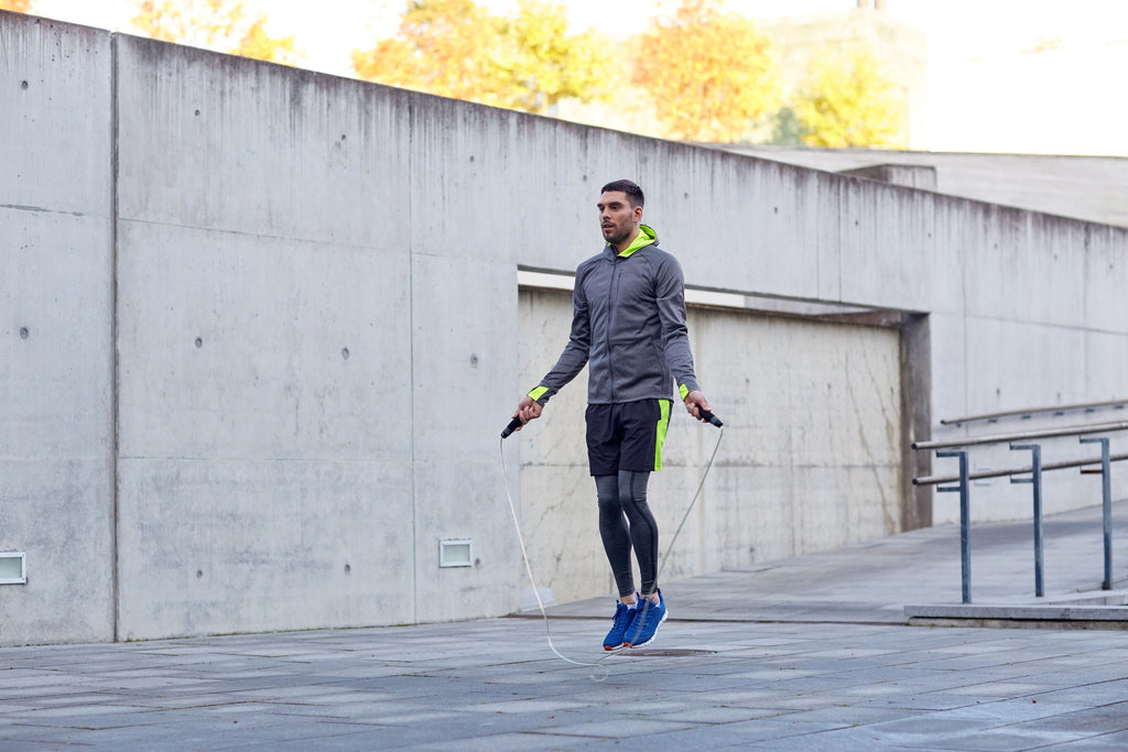 Fit man jumping rope on a rooftop