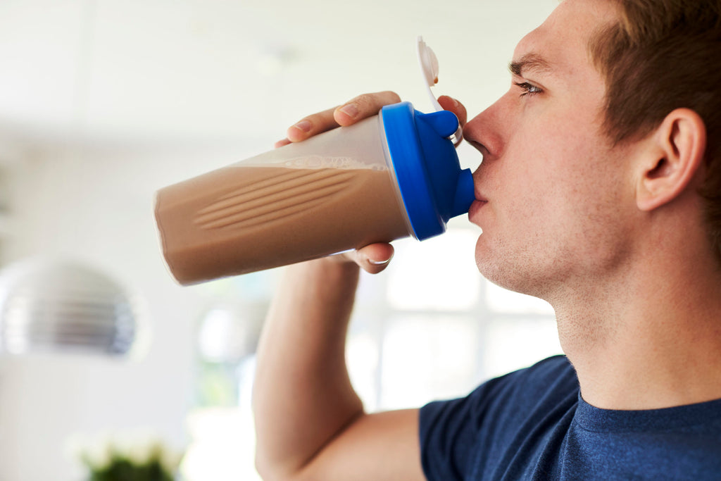Man drinking whey protein shake after workout.