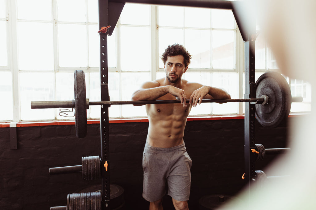 Man leaning on squat rack with barbell