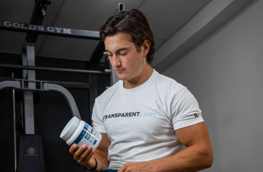 When to take BCAAS: Man looking at bottle of BCAA glutamine