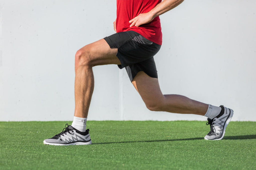 Can you build muscle without weights: Man's legs lunging across grass