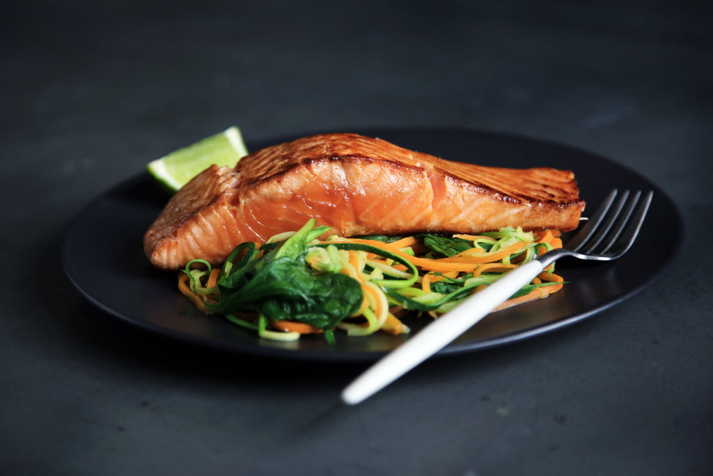 A large piece of cooked salmon over steamed vegetables sitting on a black plate with a modern white fork