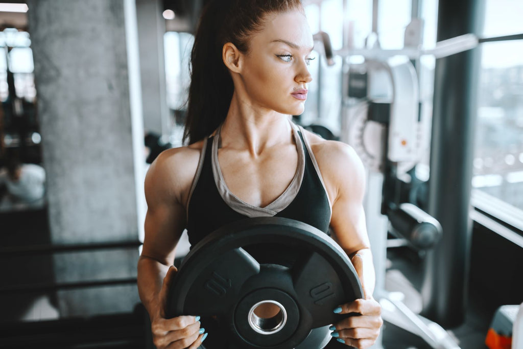 Female muscle growth: Female athlete by weights machines