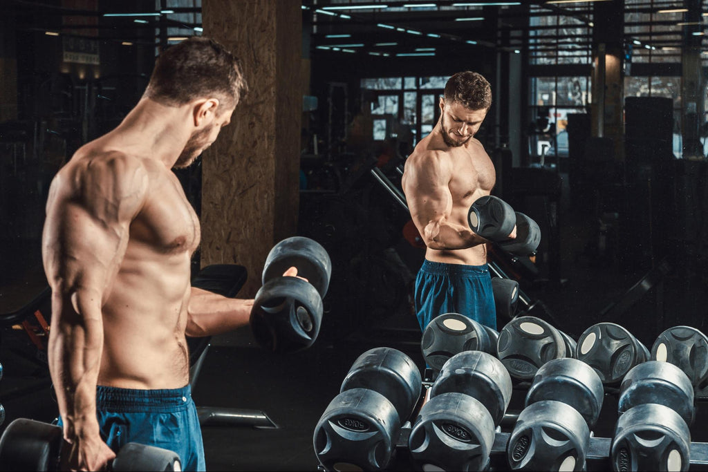 how to get bigger biceps: Man lifting weights in front of mirror