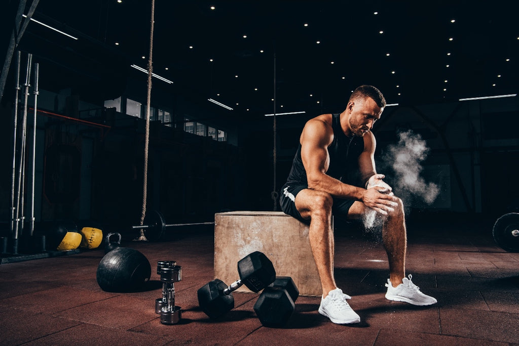 Best CoQ10 supplement: Athletic man sitting on cube with gym equipment around