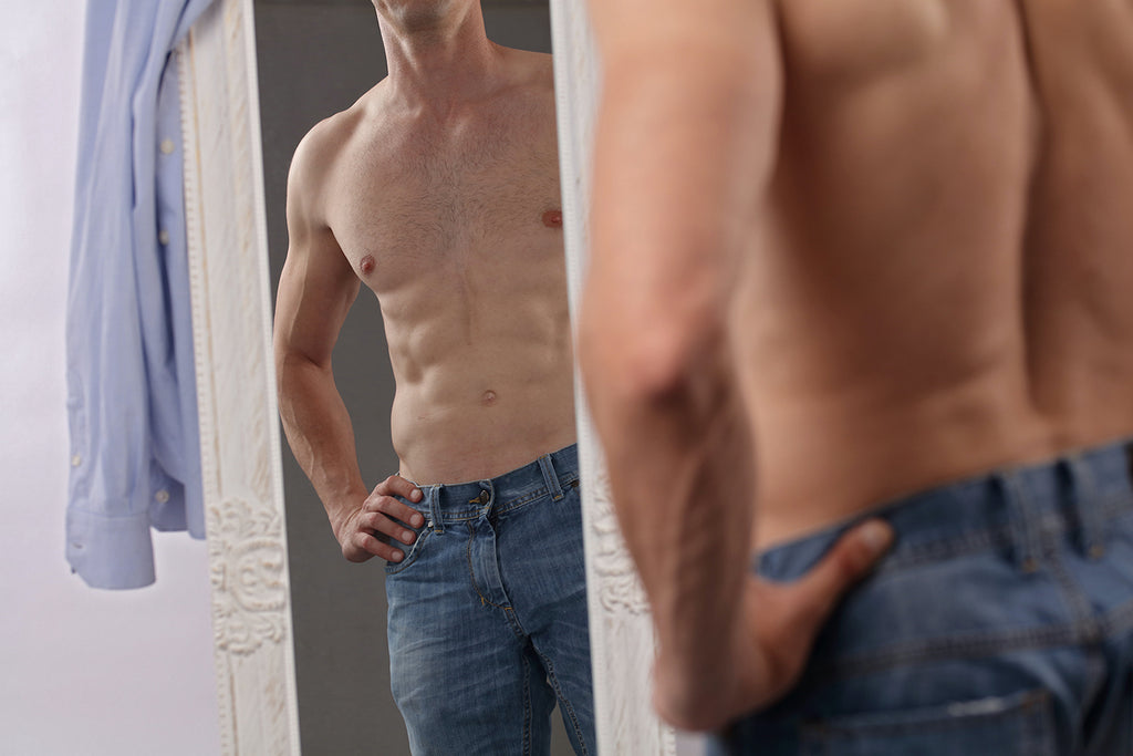 Man admiring his muscles in mirror