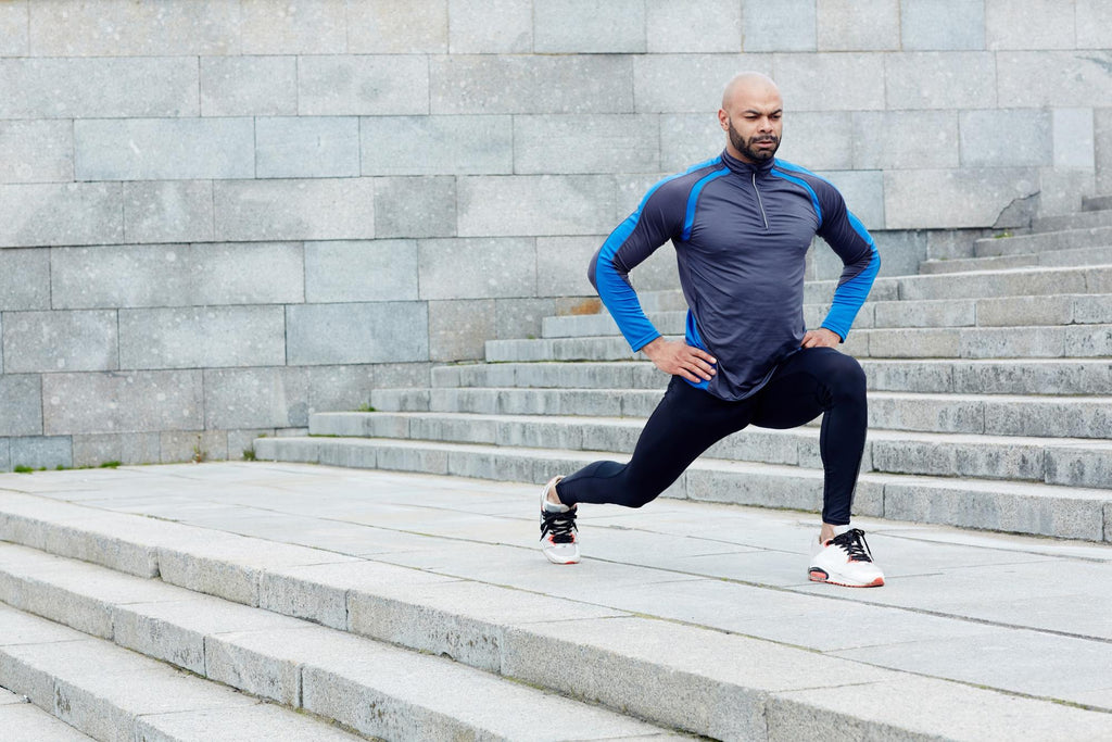 Full body workout at home: man stretching in the stairs