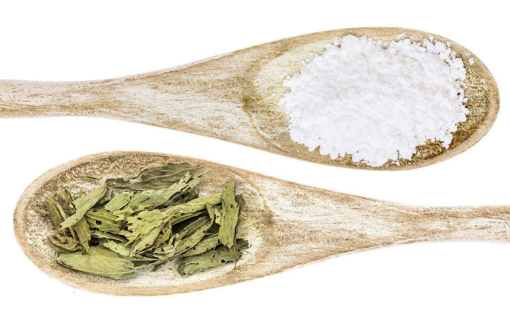 Stevia leaf and White sugar on wooden spoons