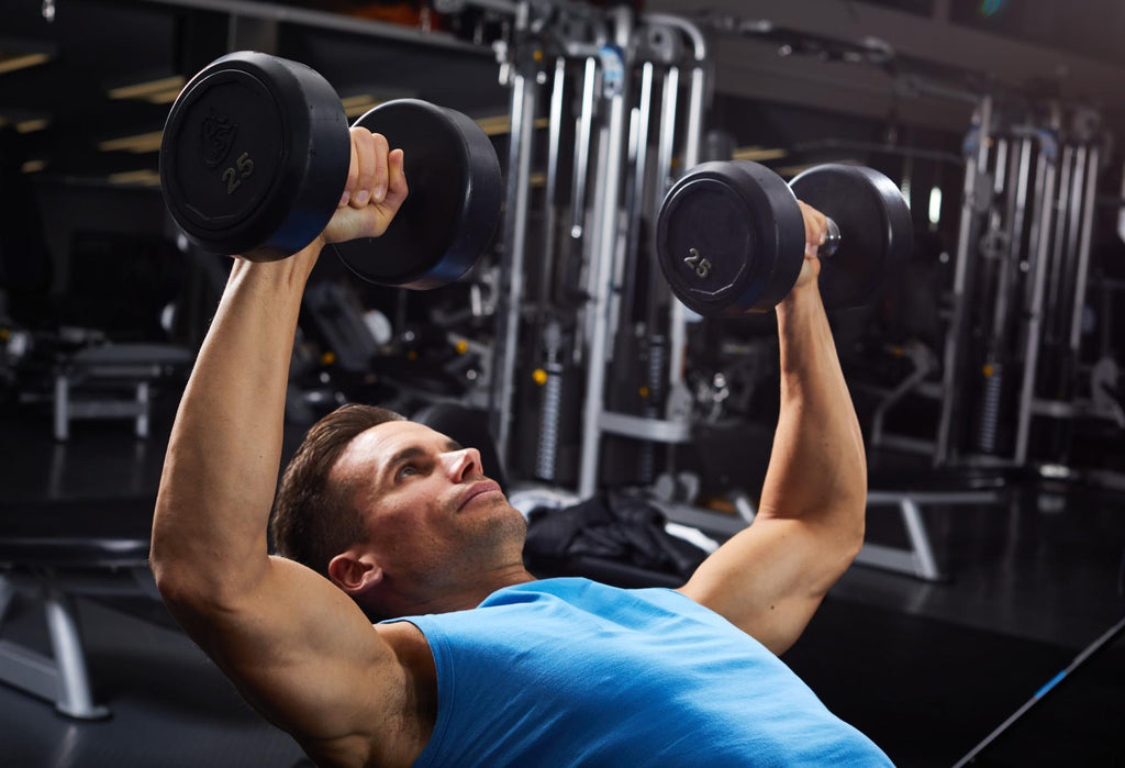 Man in the gym lifting dumbbells
