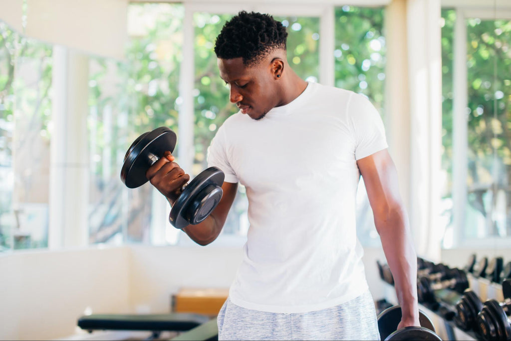 Full body workout at home: Man standing and lifting a dumbbell