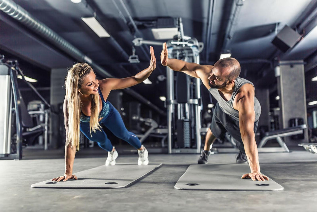 Man and woman doing plank in the gym