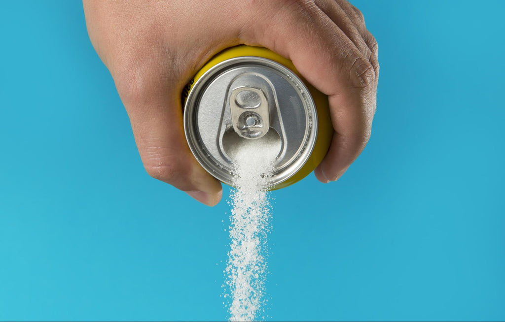 Is Splenda bad for you: Hand holding a soda can and pouring sugar