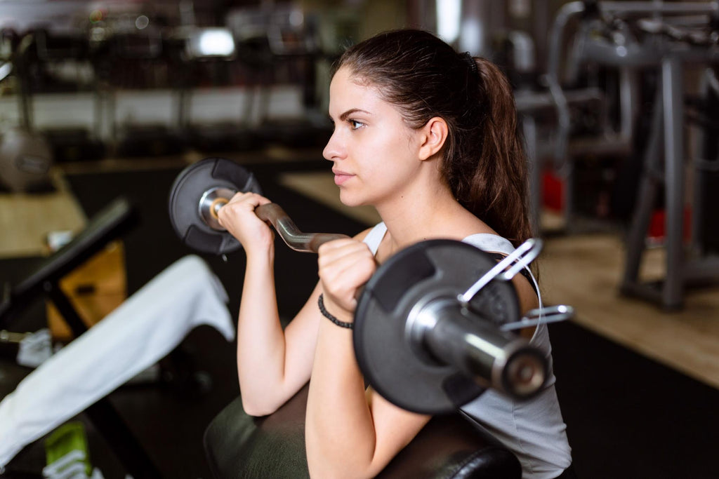 how to get bigger biceps: Woman doing preacher curls