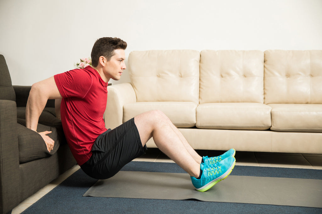 Man doing triceps dips using a couch at home