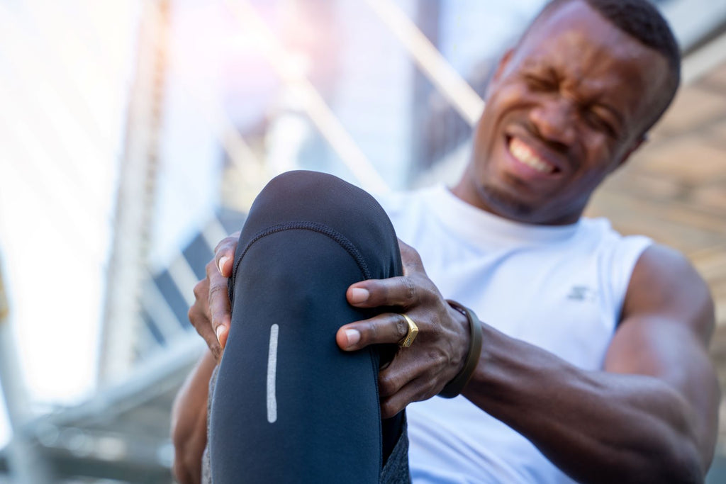 Joint supplements: Man holds knee in pain during workout