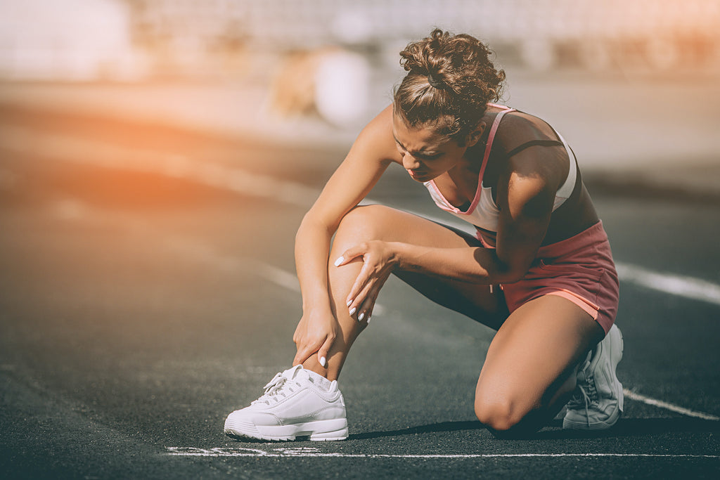 Krill oil vs. fish oil: an athlete on the track holds her ankle