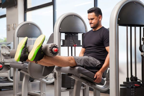 Man doing quad exercises with weights equipment