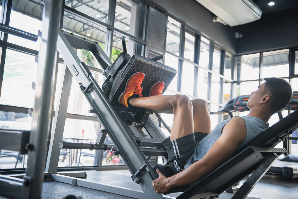 Man doing leg presses in a gym