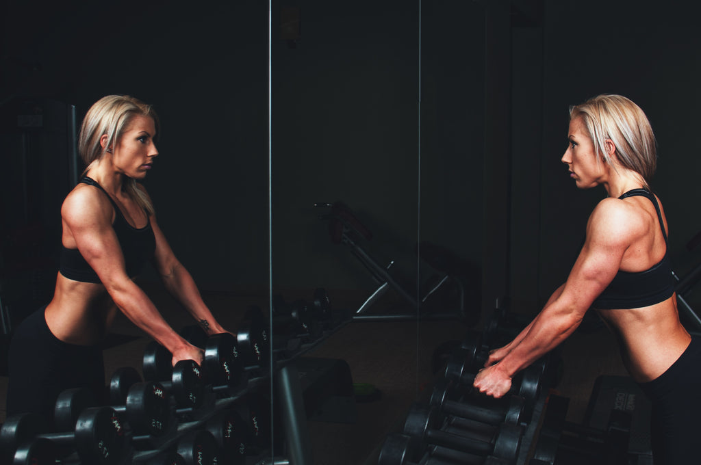 Fit woman standing in front of mirror with dumbbells ready to tackle a workout