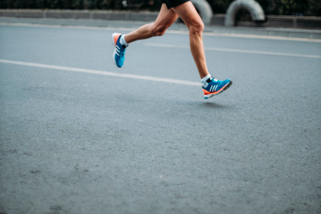 Person wearing blue adidas running shoes while running a race on paved road