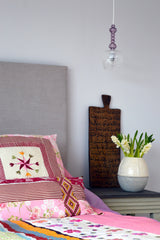 Master bedroom detail with colourful bedspread and cushion cover