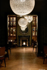 Restaurant with tables on one side and bar on the other. Large ball shaped chandeliers give a 1930's effect