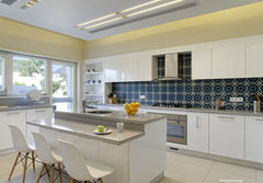 Sleek family kitchen with the bright blue, handmade, tiles as an eye catching splash back.