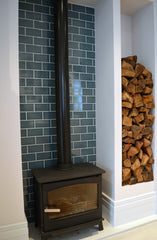 Wood burner in family kitchen against brightly tiled wall