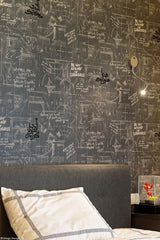 Wall in bedroom of one of the sons of the family, Andrew Martin wallpaper with Arabic calligraphy written on top.