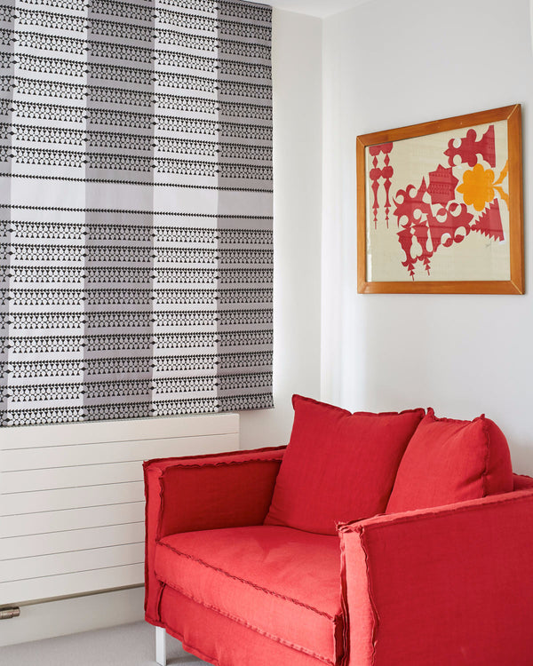 Image of the Siwa Charcoal fabric used as a blind in a room with a red chair by Designers Guild