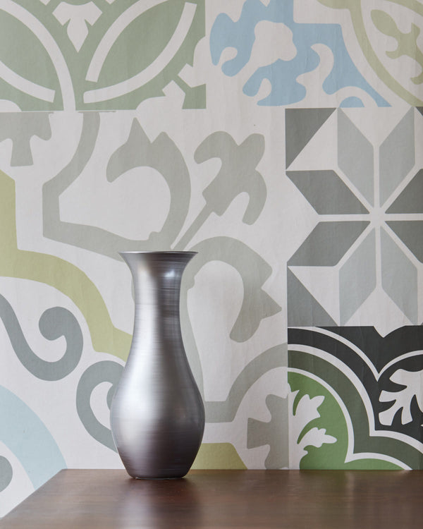 Balat Green and Blue, on a wall with a silver coloured vase on a wooden console