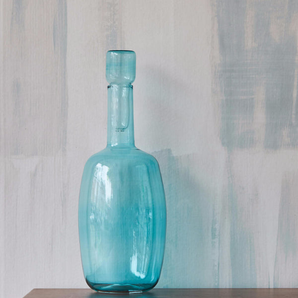 Fields Teal wallpaper on a wall with blue round bellied caraffe in front of it on wooden table
