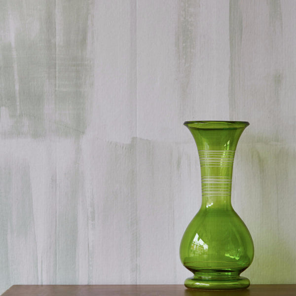 Fields lime wallpaper on wall with green vase on top of wooden table