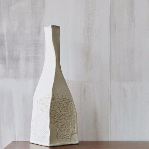 Fields Beige wallpaper with white oddly shaped ceramic vase on top of wooden table