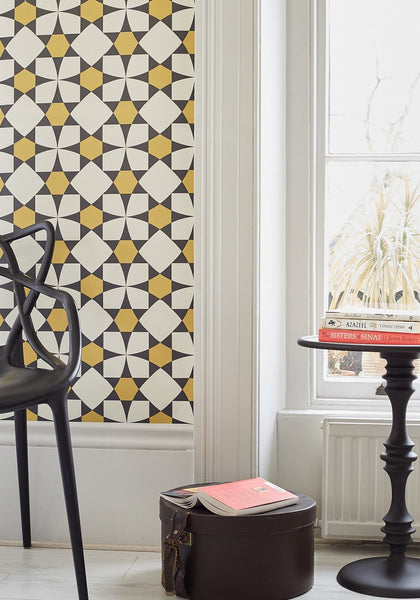 Image of a room with black chair, a side table with books against a wall with the Inlay Ochre wallpaper