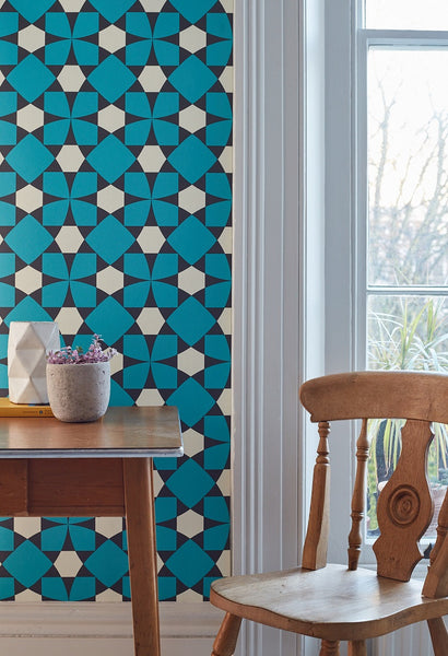 Image of a room with a wooden table and chair against a wall with Inlay Turquoise wallpaper