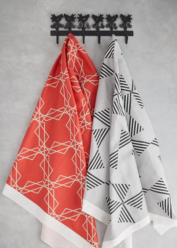 Image of a length of Stars Red and a length of Fans grey fabric hanging of a coat hook
