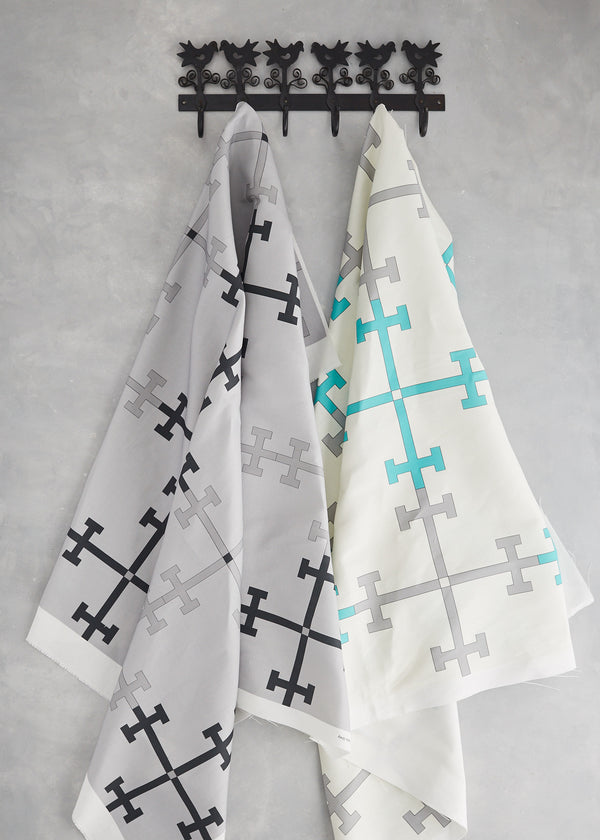 Image of a length of Trellis grey fabric and a length of Trellis Turquoise fabric hanging on a coat hook
