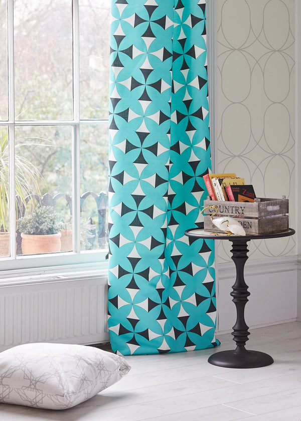 Image of a room with the Tulun Turquoise used as a curtain. In the background the Nocturn Vanilla wallpaper is visible on the wall