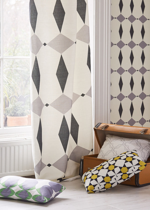 Image with the Rhombus grey fabric used as curtain. In the background the wallpaper is also Rhombus grey design, several cushions are on the floor spilling out of a suitcase
