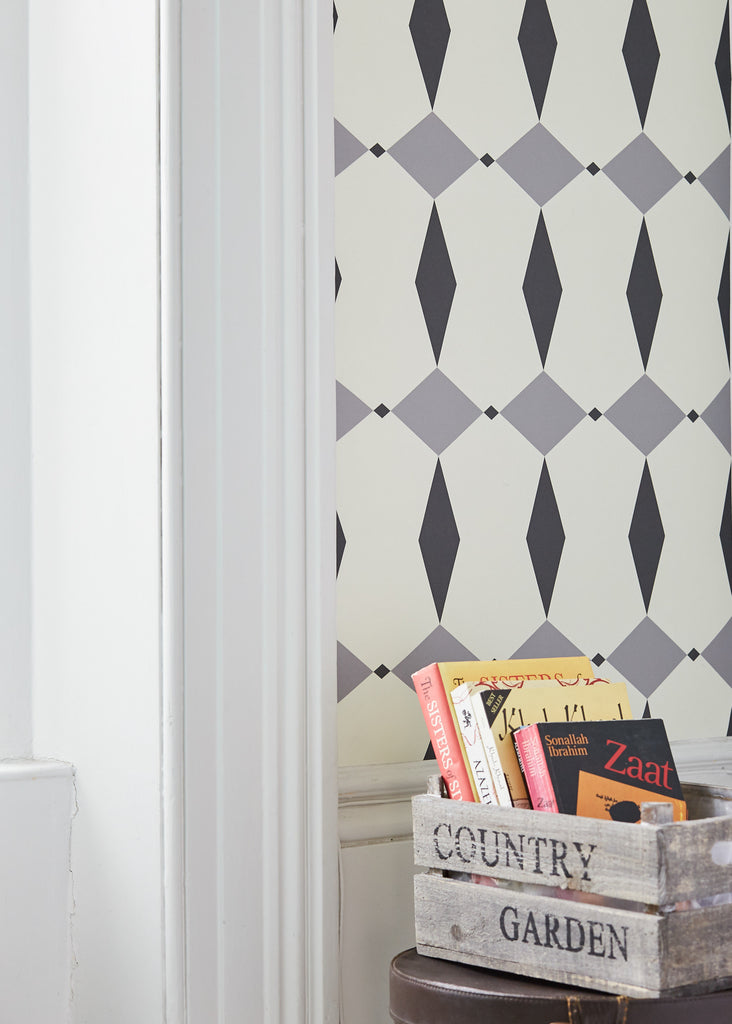 Close up of a wall with Rhombus Grey wallpaper, in the foreground is a wooden crate with books in it.
