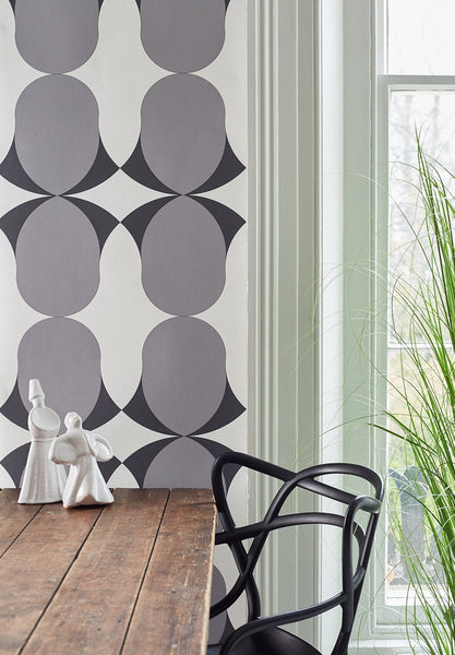 Image of a table, chair against a wall with Nocturn Grey wallpaper