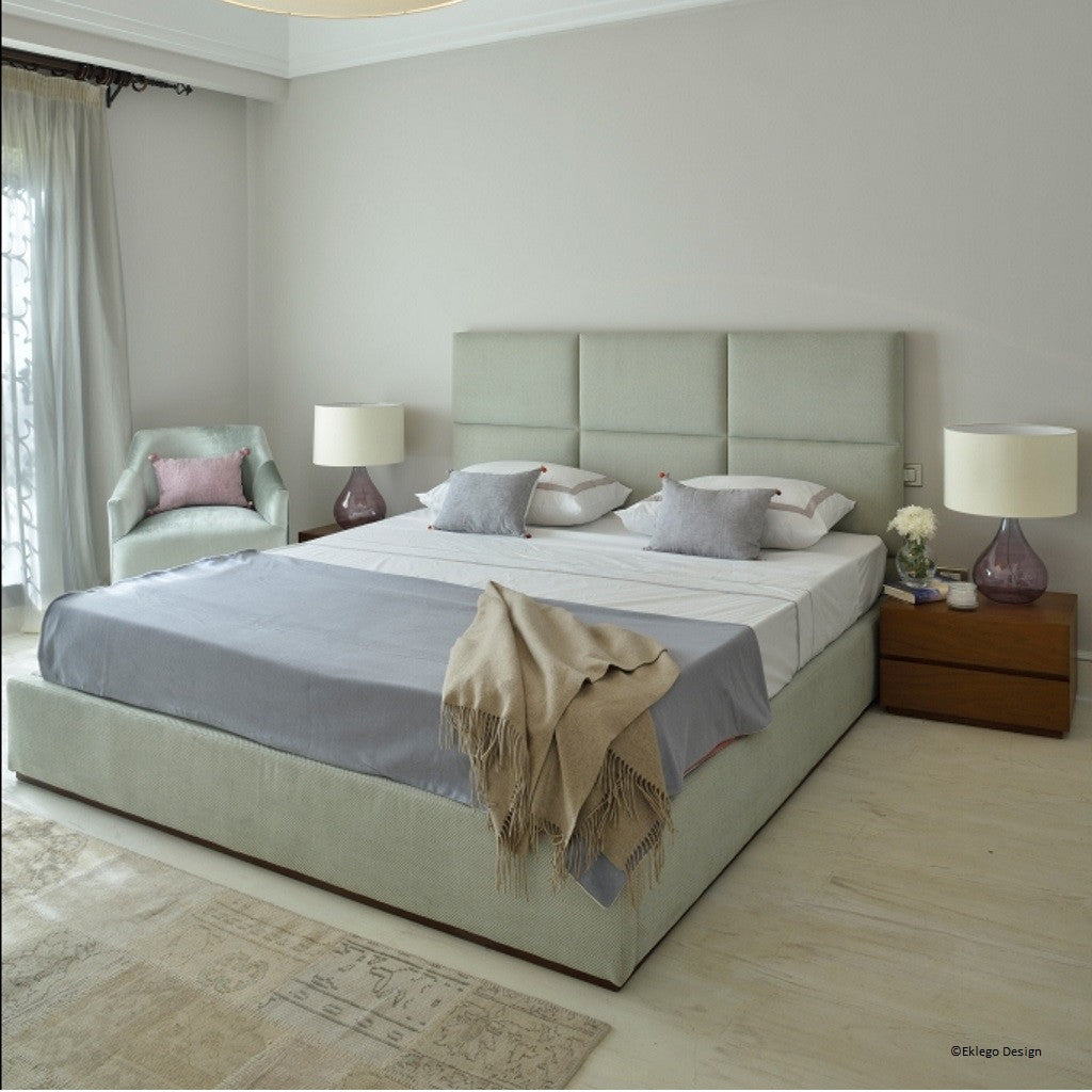 Lifestyle image of the Zen Abode bedroom set, showing the bed and its panelled headboard, the Bell chair and bedside tables.