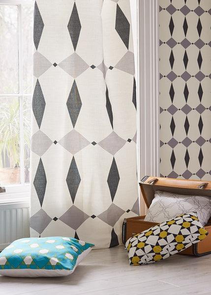 Image with a wall clad with Rhombus Grey wallpaper, a window with a Rhombus Grey curtain and a suitcase with cushions spilling out in a variety of Travels designs