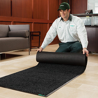UniFirst Route Service Rep delivers a clean mat to a business and rolls it out in place